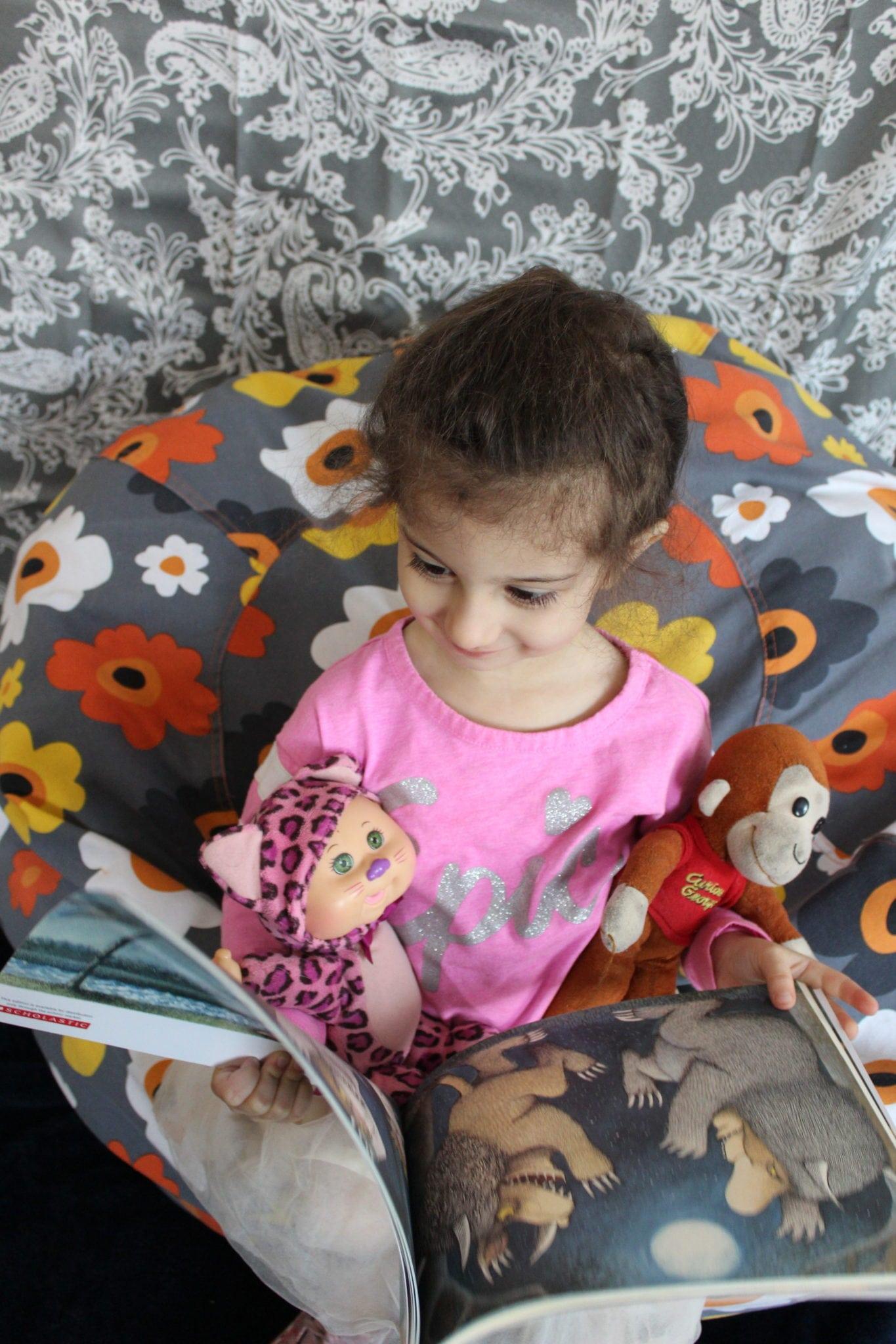 brown hair toddler reading book stuffed animals