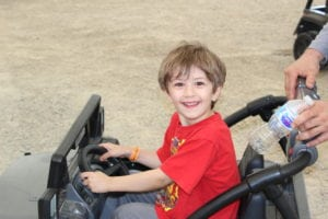 blonde boy riding motorized jeep